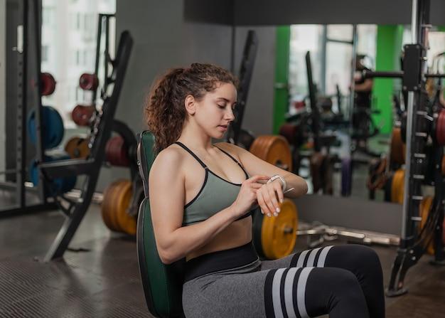 Jonge fit vrouw zittend op een bankje en kijken naar de klok zittend op een bankje in de sportschool. pauzeer tussen oefeningen