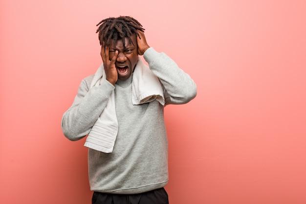 Jonge fitness afrikaanse zwarte man die troosteloos zeurt en huilt.