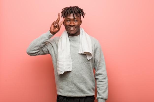 Jonge fitness afrikaanse zwarte mens die overwinningsteken toont en breed glimlacht.