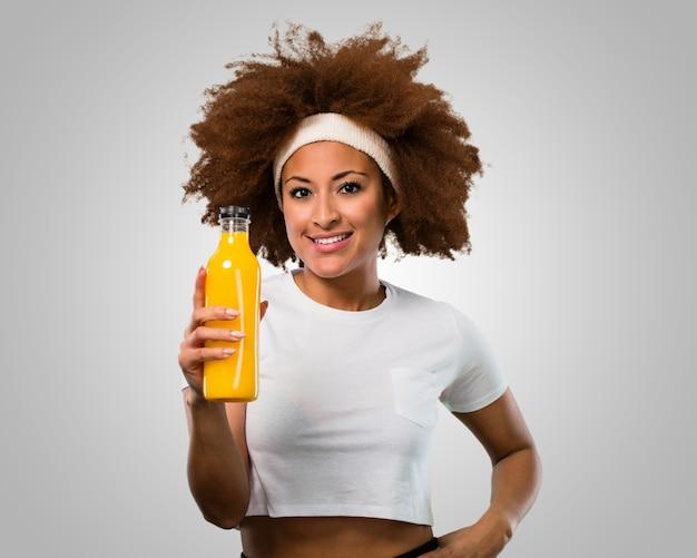 Jonge fitness afro vrouw die een jus d'orange drinkt