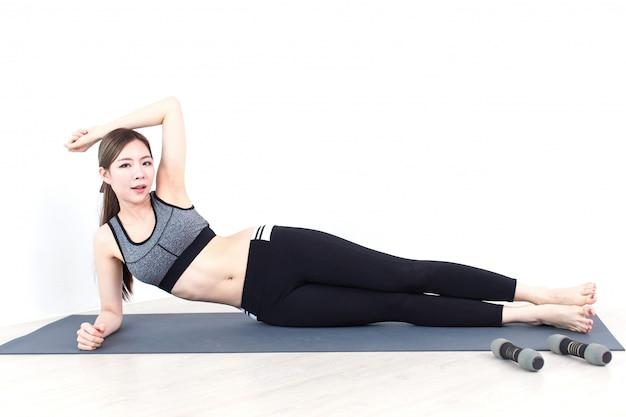 Jonge fitness aziatische vrouw die oefeningen met domoren doen, training in slaapkamer, geschiktheid, opleiding en levensstijl concept