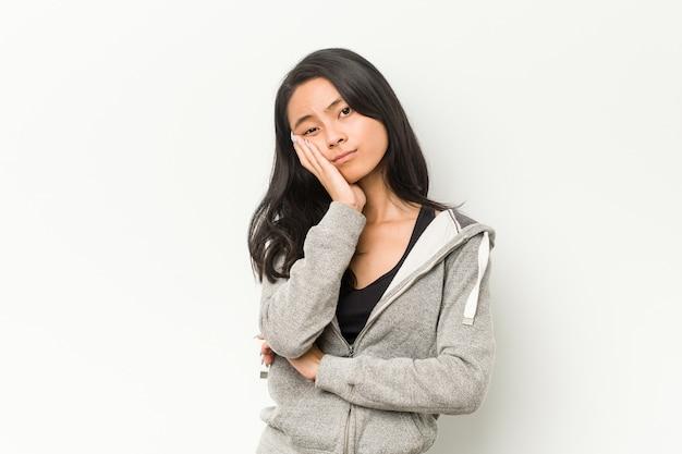 Jonge fitness chinese vrouw die zich verveelt, vermoeid is en een ontspannende dag nodig heeft.