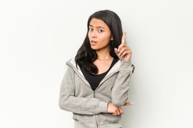 Jonge fitness chinese vrouw met een geweldig idee, concept van creativiteit.