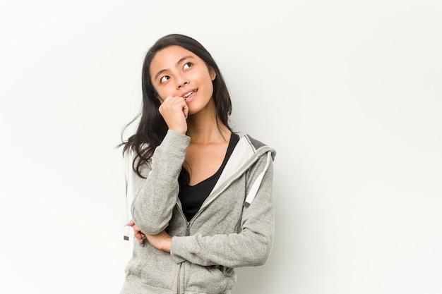 Jonge fitness chinese vrouw ontspannen denken aan iets kijken naar een kopie ruimte.