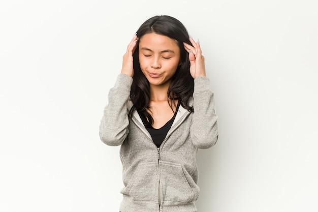 Jonge fitness chinese vrouw tempels aan te raken en hoofdpijn te hebben.