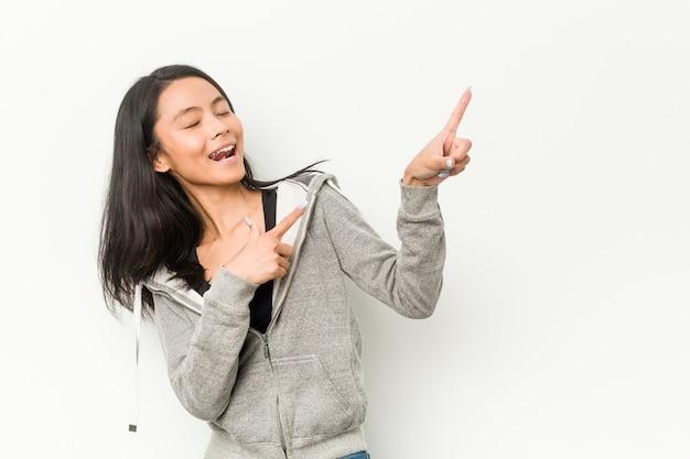 Jonge fitness chinese woman wijzend met wijsvingers naar een kopie ruimte, opwinding en verlangen uitdrukken.