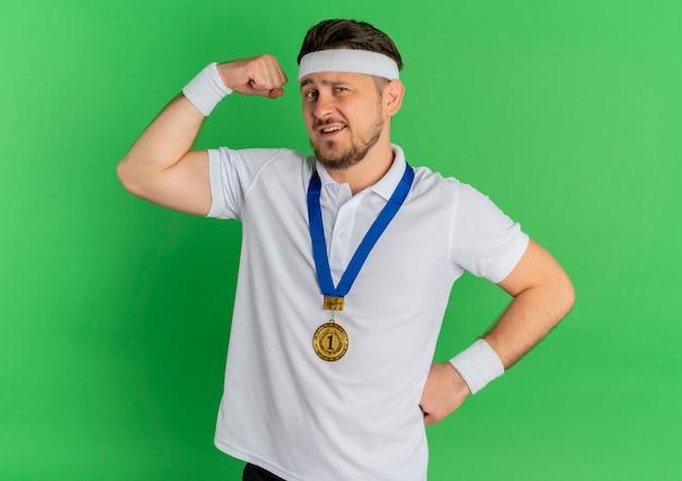 Jonge fitness man in wit overhemd met hoofdband en gouden medaille rond de nek verhogen vuist tonen biceps, winnaar concept staande op groene achtergrond