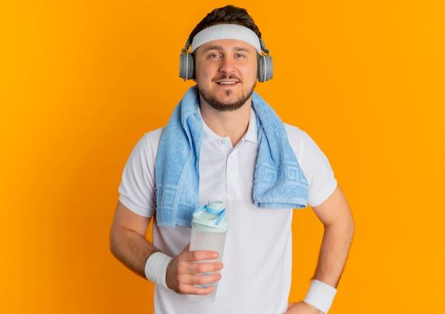 Jonge fitness man in wit overhemd met hoofdband en handdoek om de nek met fles water camera kijken met zelfverzekerde uitdrukking staande over oranje achtergrond