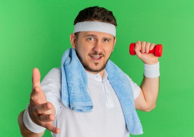 Jonge fitness man in wit overhemd met hoofdband en handdoek rond de nek uit te werken met halter camera kijken met vriendelijke glimlach staande op groene achtergrond