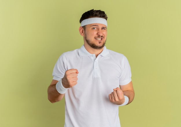 Jonge fitness man in wit overhemd met hoofdband, gebalde vuisten op zoek verward staande over olijfmuur