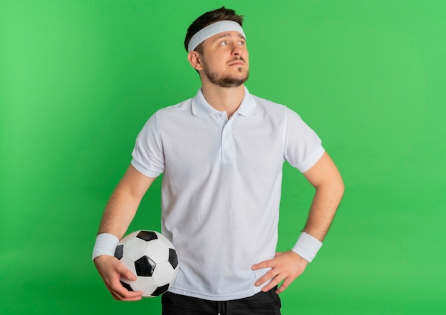 Jonge fitness man in wit overhemd met hoofdband houden voetbal opzij kijken met ernstig gezicht staande over groene achtergrond