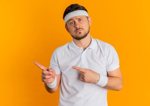 Jonge fitness man in wit overhemd met hoofdband naar voren kijkend met droevige uitdrukking op gezicht wijzend met vingers naar de zijkant staande over oranje muur