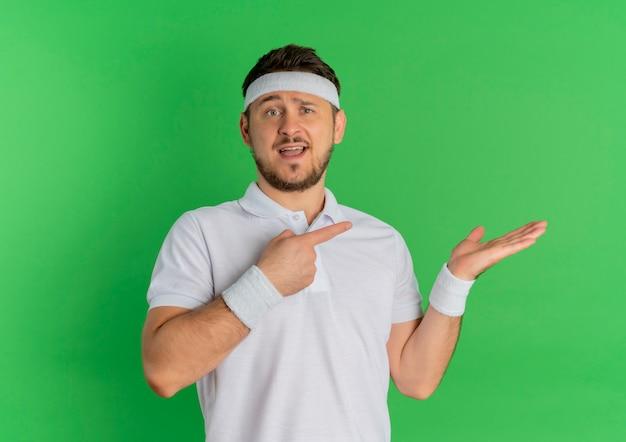 Jonge fitness man in wit overhemd met hoofdband wijzend met vinger naar de zijkant presenteren met arm van zijn hand staande over groene muur