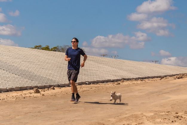 Jonge fitness man joggen met zijn puppy aan zijn zijde in het zand.