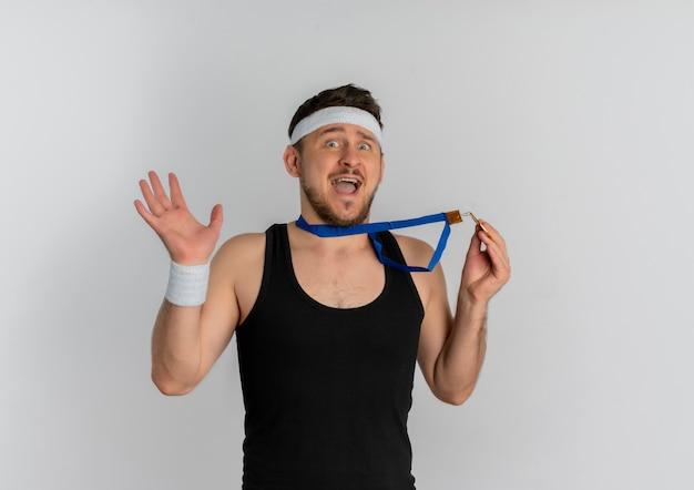 Jonge fitness man met hoofdband en gouden medaille om zijn nek kijken camera verrast en verbaasd staande op witte achtergrond
