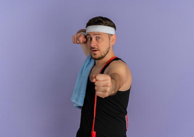 Jonge fitness man met hoofdband en handdoek op schouder met vuist naar voren concetrated staande over paarse muur