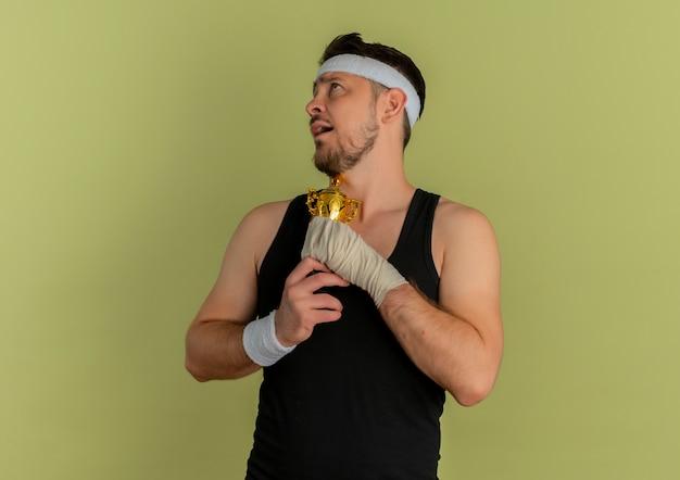 Jonge fitness man met hoofdband met zijn trofee gevoel dankbaar staande over olijf achtergrond