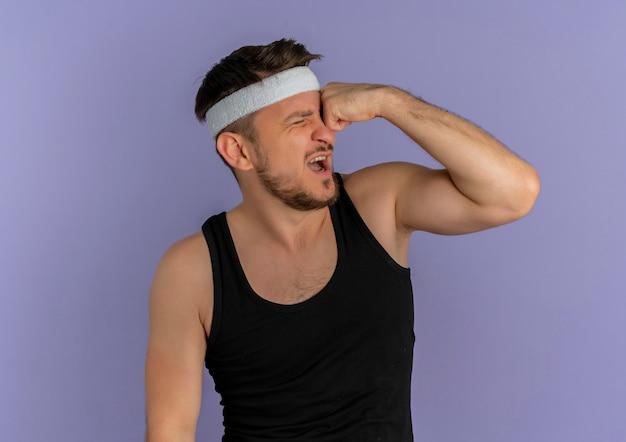 Jonge fitness man met hoofdband ponsen zichzelf op zoek verward staande over paarse muur
