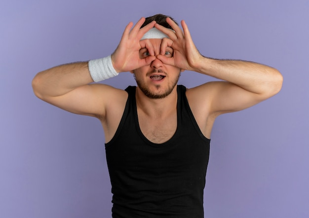 Jonge fitness man met hoofdband verrekijker gebaar maken met vingers naar voren kijken door vingers staan over paarse muur