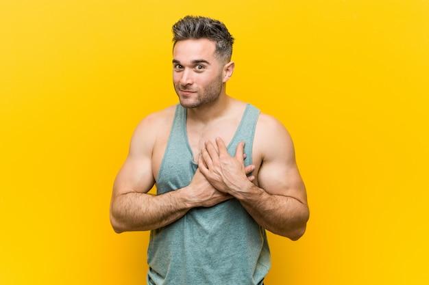 Jonge fitness man tegen een gele achtergrond heeft vriendelijke uitdrukking, palm op borst drukken.