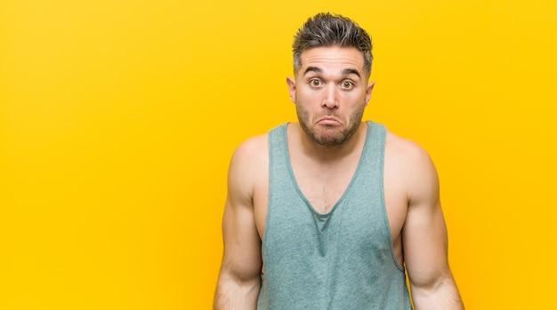 Jonge fitness man tegen een gele haalt zijn schouders op en opent verwarde ogen.