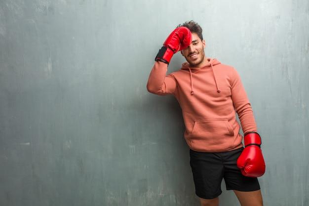 Jonge fitness man tegen een grunge muur lachen en plezier hebben, ontspannen en vrolijk