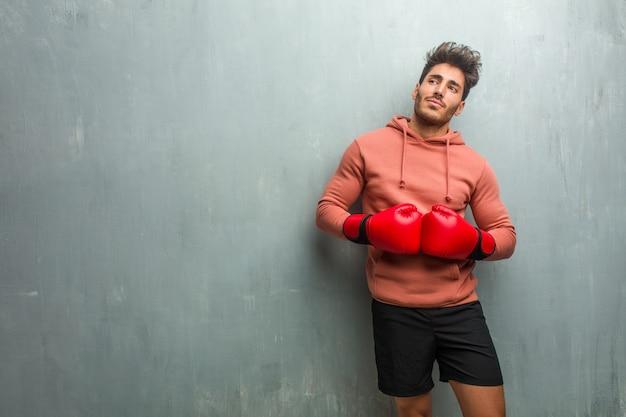 Jonge fitness man tegen een muur van de grunge opzoeken, denken aan iets leuks en met een