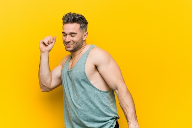 Jonge fitness man tegen geel dansen en plezier maken.