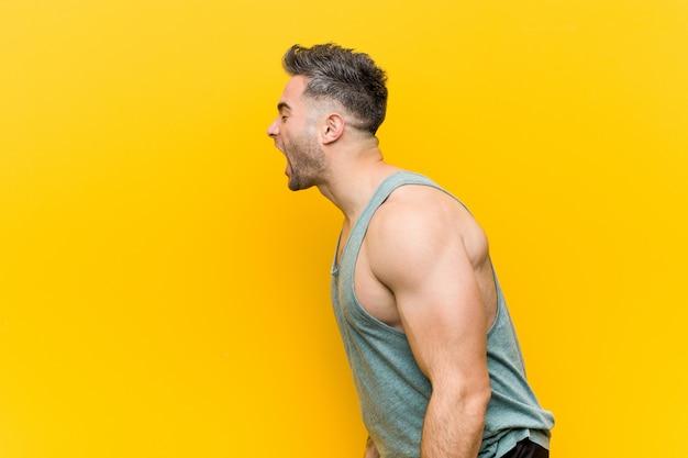 Jonge fitness man tegen geel schreeuwen naar a