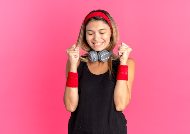 Jonge fitness meisje in zwarte sportkleding en rode hoofdband met koptelefoon balde vuisten blij en opgewonden staande over roze muur