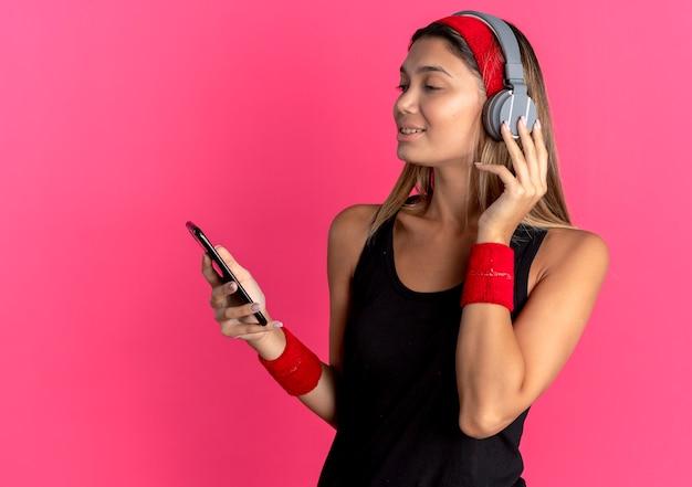 Jonge fitness meisje in zwarte sportkleding en rode hoofdband met koptelefoon kijken screnn van haar smartphone muziek zoeken over roze