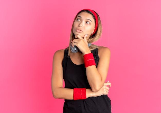 Jonge fitness meisje in zwarte sportkleding en rode hoofdband met koptelefoon opzij kijken met hand op kin verbaasd over roze