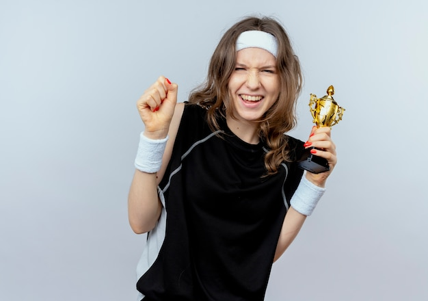 Jonge fitness meisje in zwarte sportkleding met hoofdband bedrijf trofee balde vuist blij en opgewonden staande over witte muur