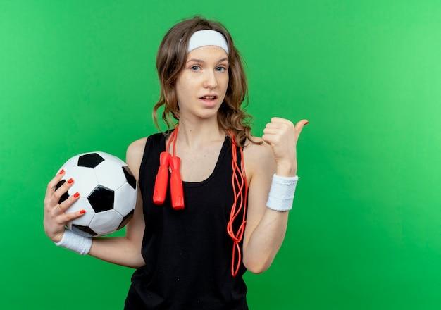 Jonge fitness meisje in zwarte sportkleding met hoofdband en springtouw rond de nek met voetbal verward wijzend terug staande over groene muur