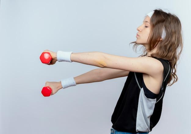 Jonge fitness meisje in zwarte sportkleding met hoofdband trainen met halters op zoek zelfverzekerd zijwaarts staande over witte muur