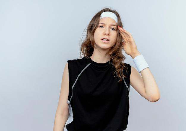 Jonge fitness meisje in zwarte sportkleding met hoofdband verward met hand boven het hoofd denken twijfels staande over witte muur