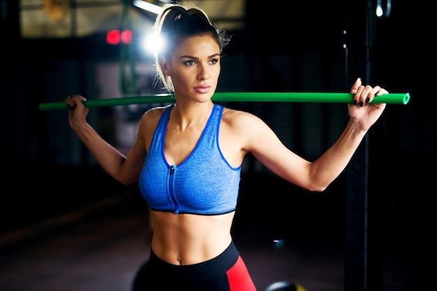 Jonge fitness meisje oefenen met een balk in de sportschool.