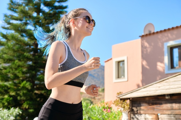 Jonge fitness meisje tiener draait op bergweg, prachtige zonsondergang landschap-achtergrond. sport, gezondheid, schoonheid, jeugd en adolescenten