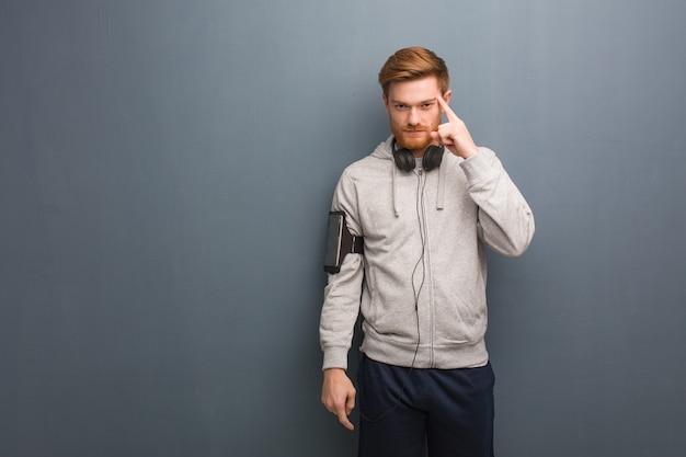 Jonge fitness roodharige man na te denken over een idee