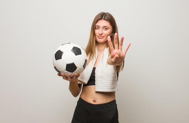 Jonge fitness russische vrouw die nummer vier toont. een voetbal vasthouden.