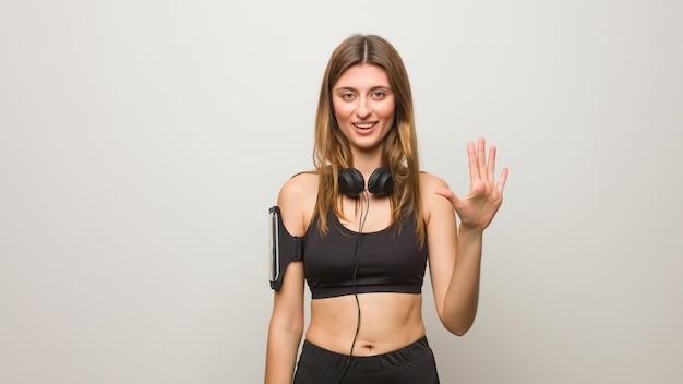 Jonge fitness russische vrouw die nummer vijf toont