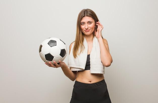 Jonge fitness russische vrouw die oren behandelt met handen. een voetbal vasthouden.