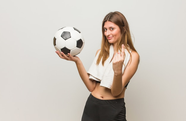 Jonge fitness russische vrouw die uitnodigt te komen. een voetbal vasthouden.