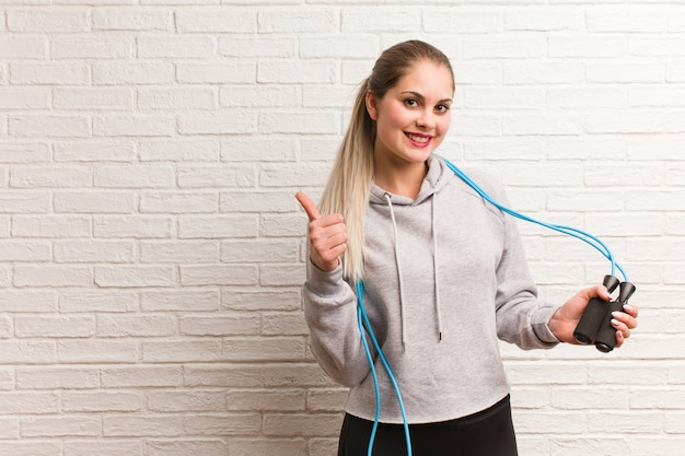 Jonge fitness russische vrouw met een springtouw tegen een bakstenen muur