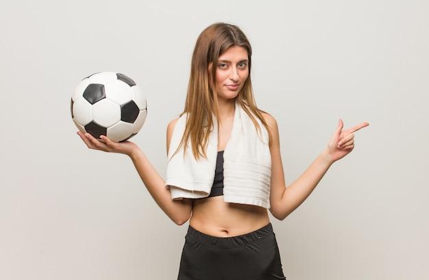 Jonge fitness russische vrouw wijst naar de kant met vinger holding een voetbal.