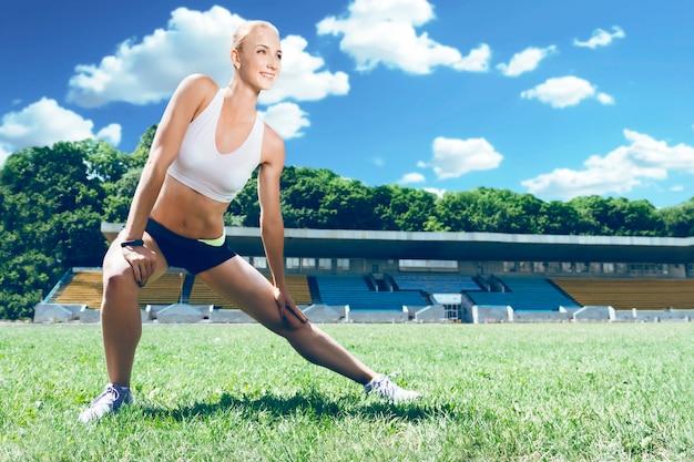Jonge fitness spier sportieve runner vrouw voorbereiding voor een run.