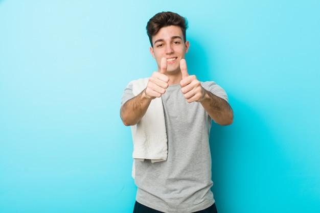 Jonge fitness tiener man met thumbs ups, cheers over iets, steun en respect.