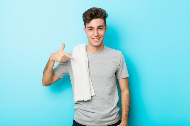 Jonge fitness tiener man persoon wijst met de hand naar een shirt kopie ruimte, trots en zelfverzekerd