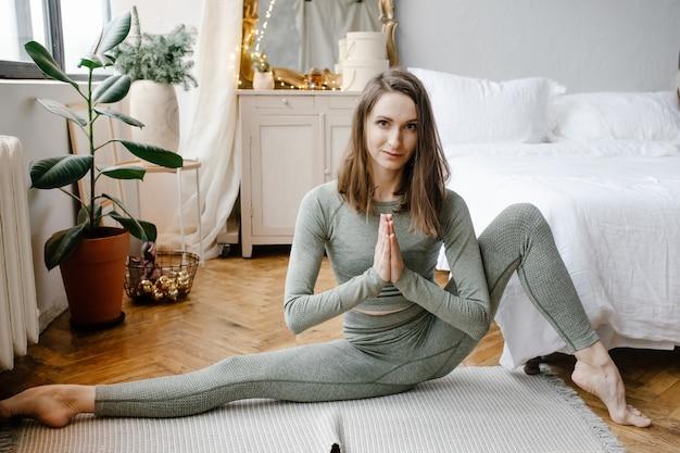 Jonge fitness vrouw beoefenen van yoga op de vloer in de slaapkamer thuis in de ochtend