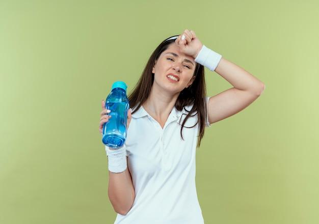 Jonge fitness vrouw die in de fles water van de hoofdbandholding verward en ontevreden over lichte achtergrond kijkt